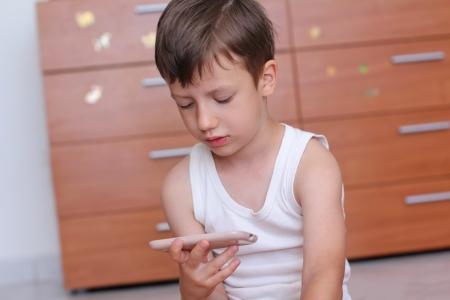 Ragazzo con lo smartphone a casa a giocare