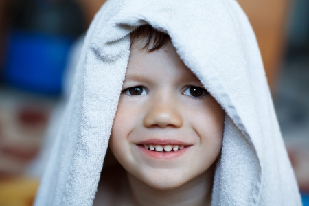 Cute child dry with towel, teeth smile photo