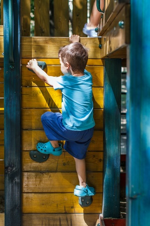jungle gym: Little boy climbing on jungle gym without rope and helmet Stock Photo