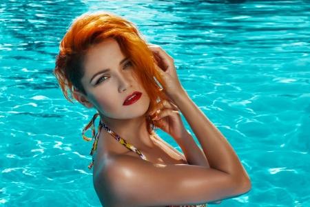 Sexy redhead woman posing in swimming pool photo