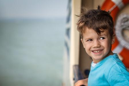 niños malos: Niño pequeño mal cerca de barandillas en la cubierta del barco de pasajeros grande Foto de archivo