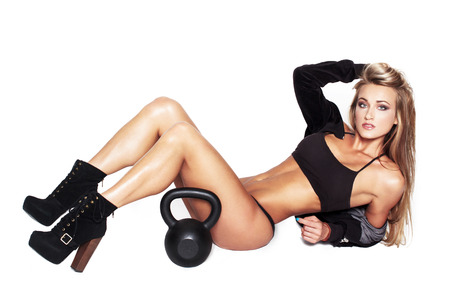 Sexy blonde fitness model with kettlebell, isolated photo