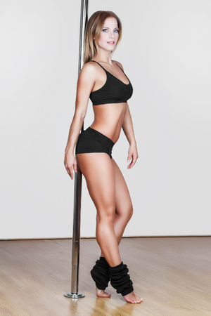 Sexy pole dancer posing in studio photo