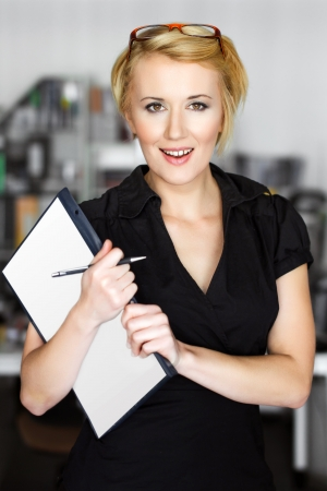 Young blonde businesswoman holding notepad and paper photo