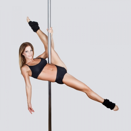 Sexy pole dancer leg up, grey empty space photo