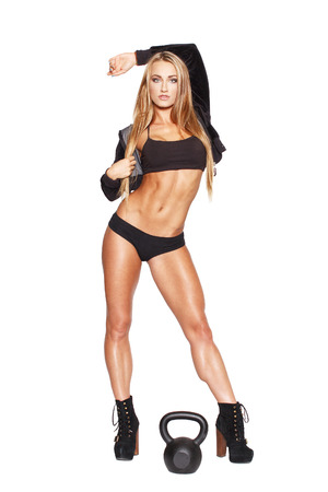 Sexy fitness model posing with kettlebell, isolated photo