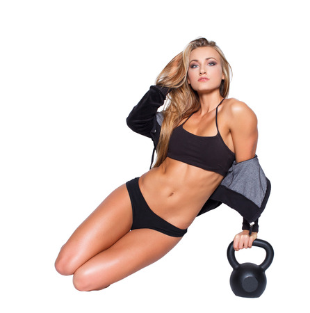 Fitness model sexy sit avec kettlebell, isol� photo