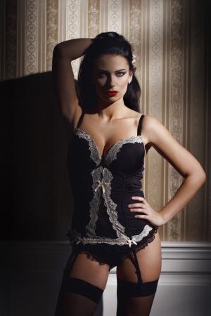 Sexy brunette woman at night posing at wall, seduction photo