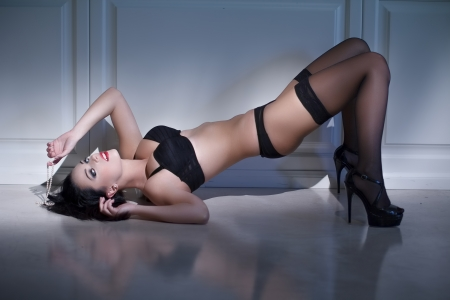 Brunette sexy woman laying on floor at night photo