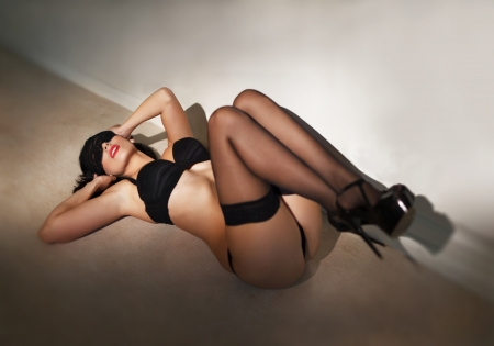Sexy brunette woman with lace eye cover posing on the floor, legs up photo