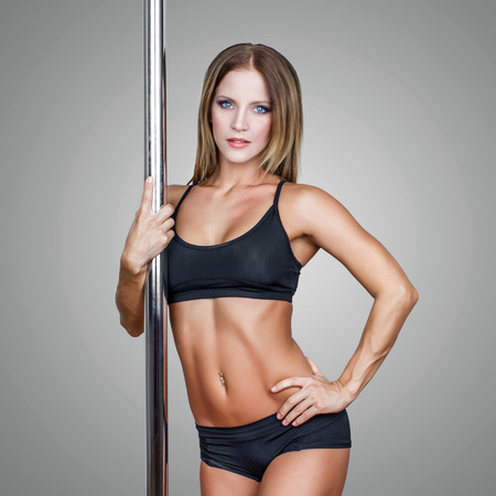 Sexy fit pole dancer posing, blue eyes photo