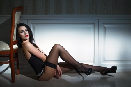 Sexy brunette model sitting on the floor at night photo