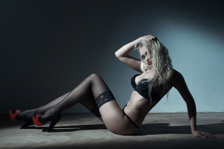 Sexy blonde woman sitting on floor at night photo