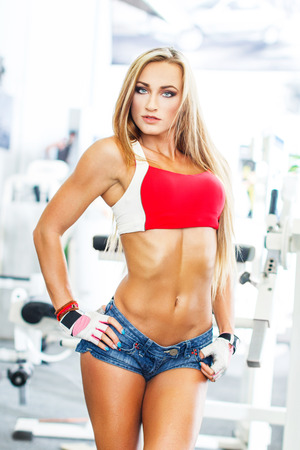 Sexy blonde fitness model posing in gym photo