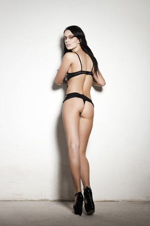 Sexy young woman showing ass, posing at wall photo