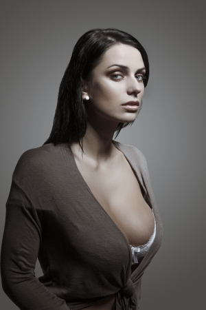 Sexy brunette woman portrait, gray background photo