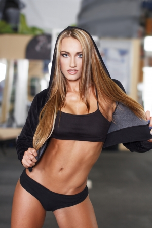 Sexy blonde fitness model in gym photo
