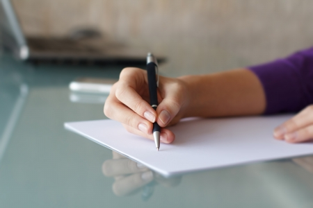 writing letter: Businesswoman writing with pen in office