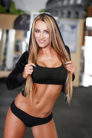 Sexy fitness model posing in gym, teeth smile photo