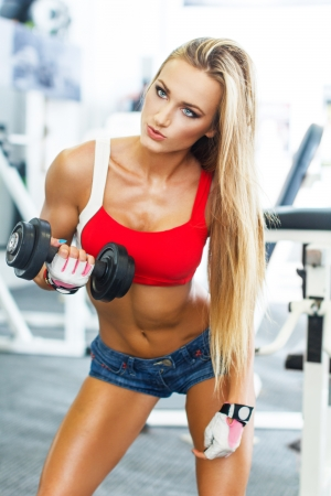 Dumbbell bicep curl by a fitness girl at gym photo