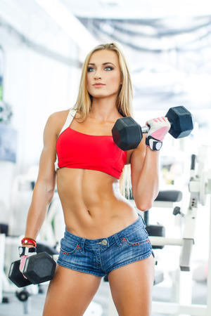 Sports woman. Woman lifting weights in a training session photo