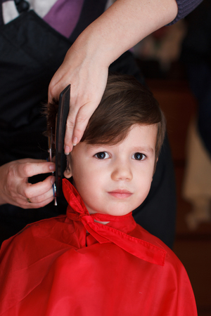 Beautiful young child with smile at the hairdresser having a haircut photo
