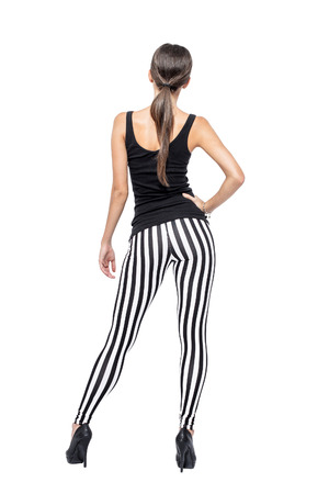 Sexy brunette woman in striped leggings and high heels from back, isolated on white background photo