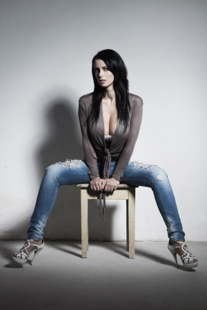 Sexy brunette with huge boobs sitting on stool photo