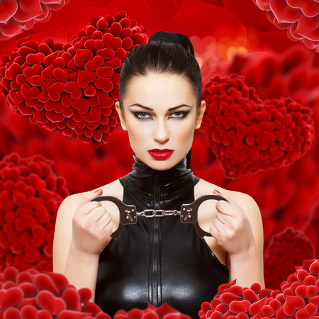Sexy dominatrix holding handcuffs, hearts background