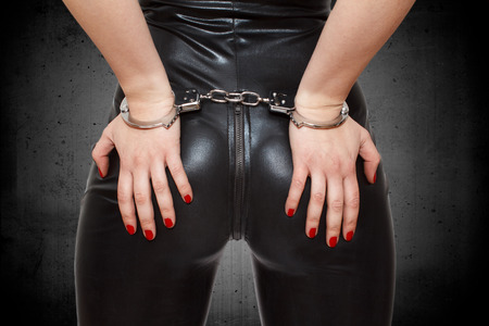 Sexy dominatrix, hands on ass in handcuffs, closeup photo