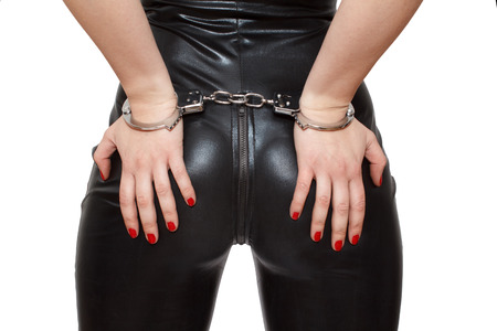 Sexy dominatrix hands on ass in handcuffs, closeup, isolated on white  photo