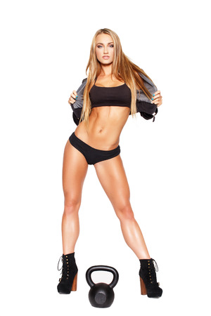 Beautiful blonde fitness model with kettlebell, isolated on white photo
