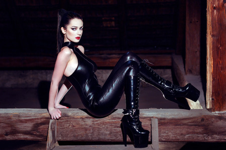 Beautiful fetish model posing on timber in high heel platform boots, seduction photo