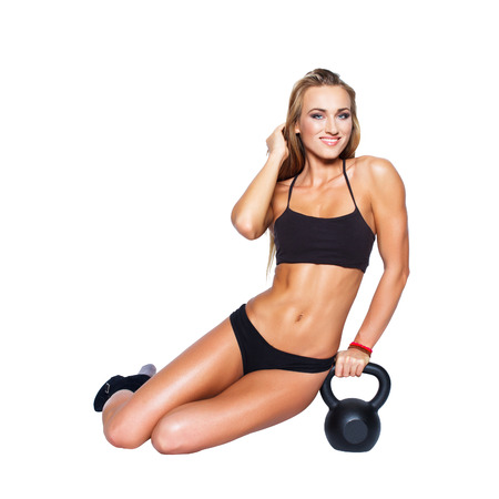 Sexy blonde fitness model with kettlebell, isolated on white background photo
