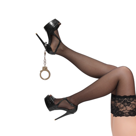 Woman legs with handcuffs, isolated on white, desire photo