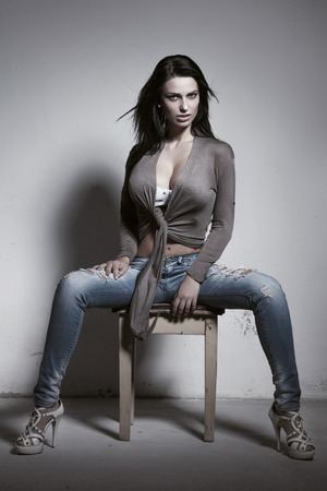 tits: Sexy brunette woman with big tits sitting on stool