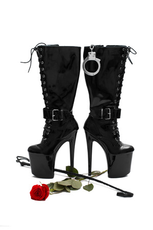 Black platform boots with whip and rose, isolated on white photo