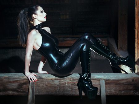 Sexy dominatrix at night posing on timber, bdsm photo
