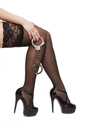 Beautiful woman legs in high heels and handcuffs, isolated on white photo