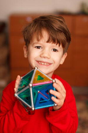 skillful: Skillful little boy holding toy, teeth smile, indoor portrait