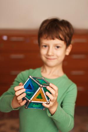 skillful: Skillful little boy holding toy, indoor portrait