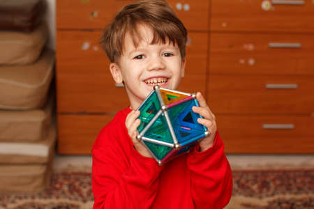skillful: Happy skillful little boy holding toy, indoor portrait Stock Photo