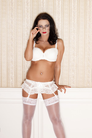 Sexy brunette woman in white underwear at vintage wall photo