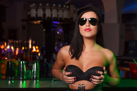 Sexy brunette woman holding tits in bar photo
