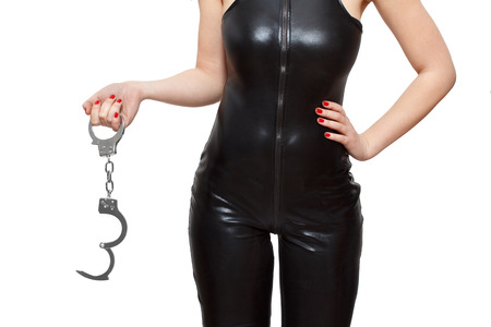 Dominatrix holding handcuffs closeup, isolated on white background photo