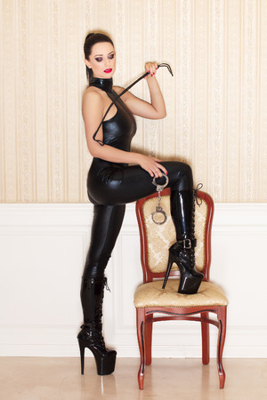 Sexy woman in latex catsuit at vintage wall, closed eyes, desire photo