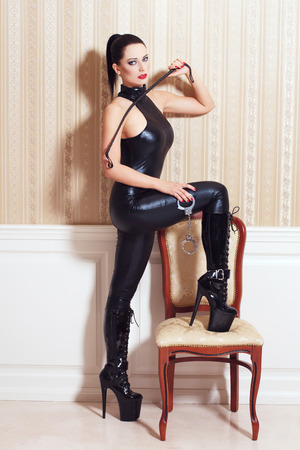 Sexy woman in latex catsuit at vintage wall, desire photo