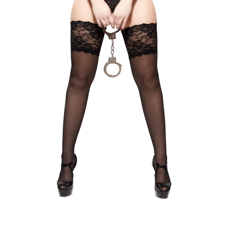 Beautiful woman legs in high heels, holding handcuffs, isolated on white photo