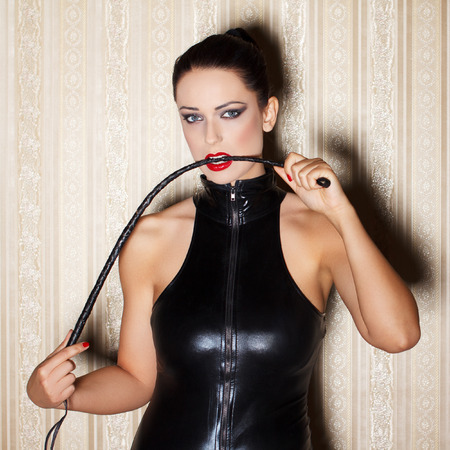 Sexy woman in latex catsuit with whip in mouth, desire photo