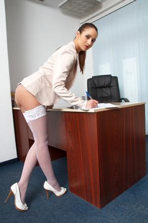 papeles oficina: Sexy secretaria en la oficina escribiendo con pluma, vista lateral